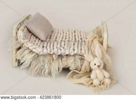 Wooden stylized small furniture bed with pillow and knitted blanket for newborn photoshoot in beige colors. Designed decoration object for infant studio photo