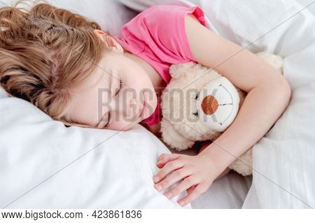 Little beautiful girl lying in the bed hugging teddy bear and sleeping. Preteen child resting wearing pink t-shirt and holding toy. Closeup portrait of cute female kid napping