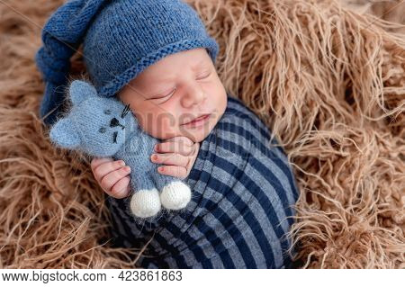 Adorable newborn baby boy swaddled in toby fabric holding in his tiny hands knitted toy and smiling during sleeping. Cute infant kid wearing hat napping in fur during studio photoshoot.