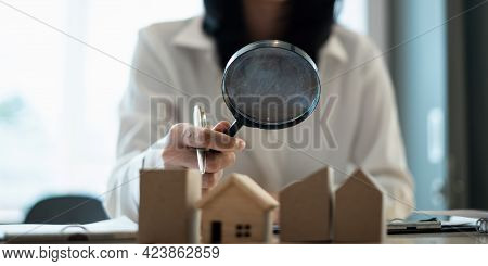 A Woman Holding Magnifying Glass And Checking House Model .real Estate House Appraisal And Inspectio