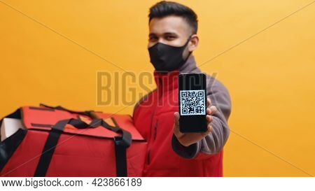 Delivery Man Wearing Black Mask Holding Red Parcel Box. Showing Mobile Phone Screen In The Camera Wi
