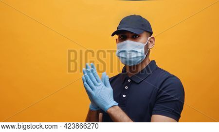 Young Indian Man Wearing Mask And Gloves Taking Precautions. Dressed In Blue Polo And Blue Cap. Conc