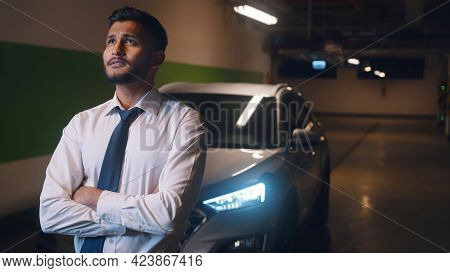 Indian Man Standing In The Parking Lot With His Car Parked Behind Him. Stressed Out Man Dressed In F