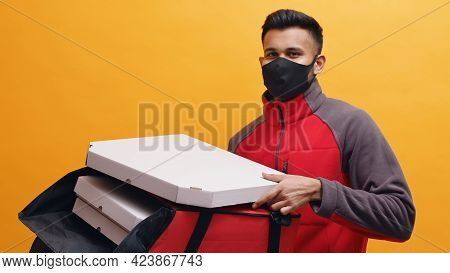 Delivery Boy Wearing Black Mask And Carrying Pizza Boxes In His Red Parcel Box. Concept Of Home Deli