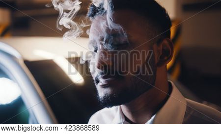 Young Indian Guy Smoking In The Parking Lot. A White Car Can Be Seen Parked In The Background.concep