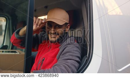 Delivery Guy Wearing Red Uniform Sitting In The White Van And Tipping His Cap. Happy Indian Guy Sitt