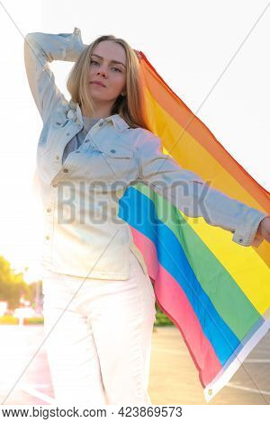 Young Blonde Millennial Woman With Lgbtq Flag Outdoor. Rainbow Lgbt Flag. Peace And Freedom The Symb
