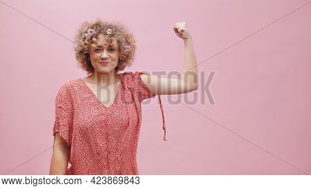 Beautiful Girl With Curly Hair Showing Her Strong Arm. Dressed In Casual Pink Top And Wearing Flower