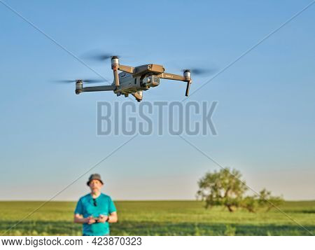 Briggsdale, CO, USA - June 8, 2021:  Radio controlled DJI Mavic 2 Pro quadcopter drone is flying over green prairie with a male pilot in background.