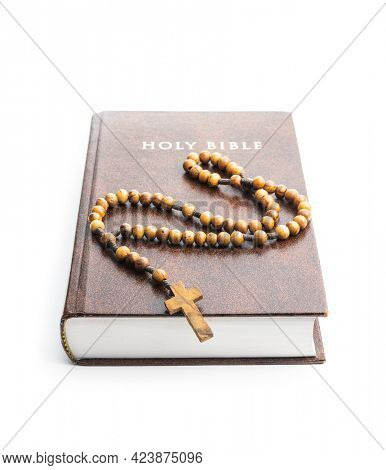 Holy bible and wooden rosary beads isolated on a white background.
