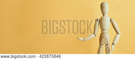 Wooden Doll With Gesture On Yellow Background. Mannequin Shows Gesture. Figure Of Wooden Human With