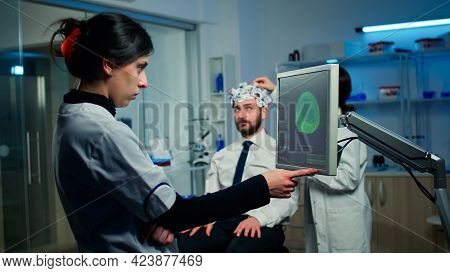 Woman Researcher Looking At Monitor Analysing Brain Scan While Coworker Discussing With Patient In B