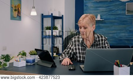 Mature Woman Using Tablet And Laptop In Same Time Analysing Financial Graphs Working From Home Sitti