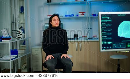 Stressed Patient Sitting On Chair In Neurological Laboratory Waiting For Medical Researcher Investig