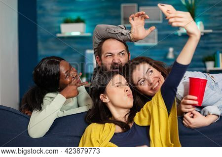 Multi-ethnic Friends Bonding Together Taking Pictures Making Diverse Expression Posting On Social Me