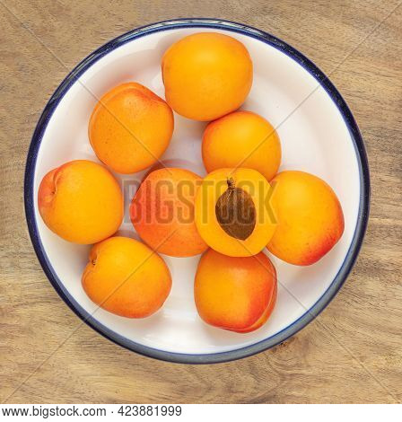 Fresh Apricot Fruits On White Plate Over Wooden  Background. Sweet Apricots Pile, Top View
