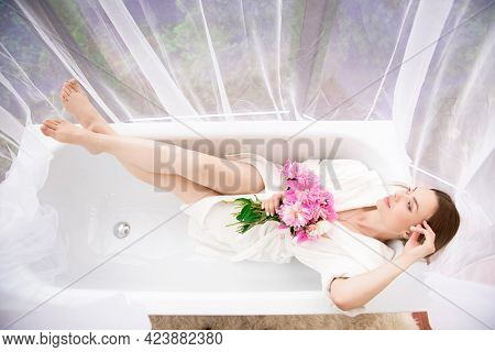 Beautiful Girl In A White Bathrobe With A Bouquet Of Pink Peonies Near The Bath.