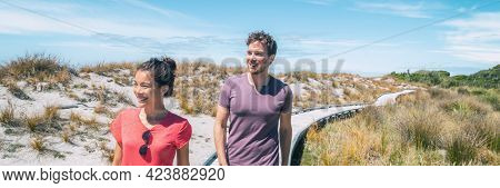 Couple tourists walking on Ship Creek beach boardwalk on summer travel vacation in West Coast, South Island of New Zealand. Panoramic banner