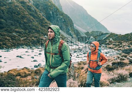 Hiking - hikers on trek with backpacks living healthy active lifestyle. Hiker girl walking on hike in mountain nature landscape