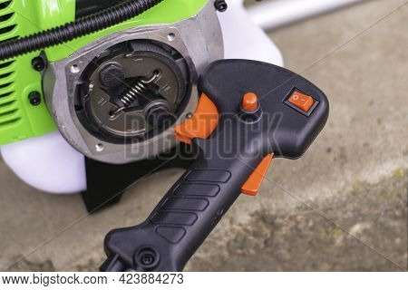 The Engine Of The New Garden Trimmer With The Unscrewed Rod And The Control Handle Of The Trimmer Cl