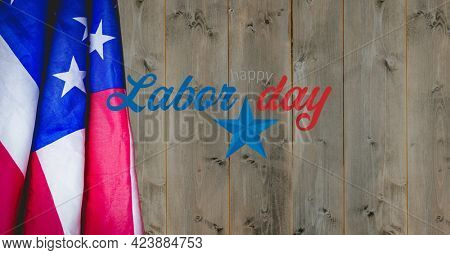 Happy labor day text and american flag against wooden background. american labor day template background design concept
