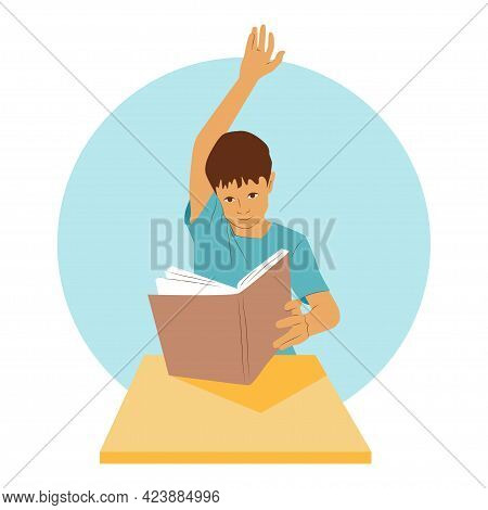 Young Student Sits At A Desk And Holds A Book. School Boy Raises His Hand Up To Give An Answer. Clev