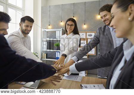 Team Of Happy People Joining Their Hands Standing Around Table In Business Meeting