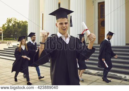 Happy University Graduate Standing With Diploma In Hand Over Fellow Students Walking At Background