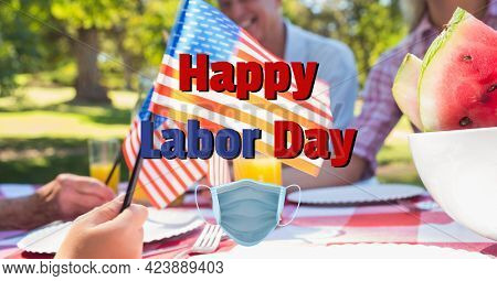 Composition of text happy labor day and face mask over happy family at picnic waving american flags. patriotism, independence and celebration concept digitally generated image.