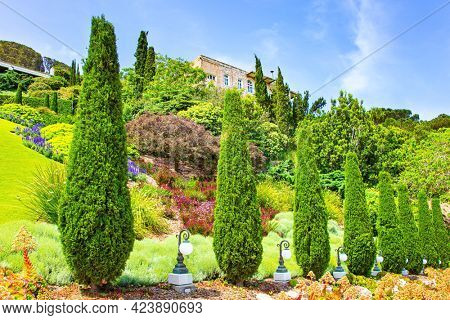 Gorgeous colorful gardens, flower beds, cypress trees and green lawns attract pilgrims and tourists. Israel. View from Mount Carmel to the international seaport of Haifa. Clear sunny day