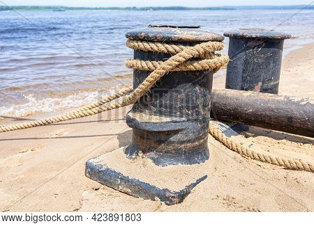 Mooring Bollard With A Fixed Rope In The Harbor On The Sand Beach