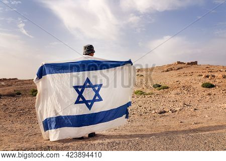 Israeli Military Infantry Stands In The Middle Of The Desert Holding An Israeli Flag With The Star O