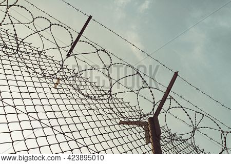 Barbed Wire Steel Wall Against Immigations. Wall With Barbed Wire On The Border Of 2 Countries. Priv