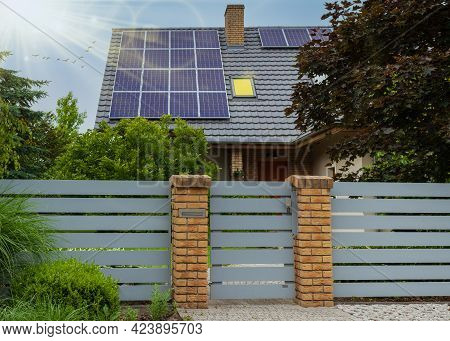 Solar Panels On A Roof. Modern House And Solar Energy. Rays Of The Sun And Lots Of Greenery. Light I