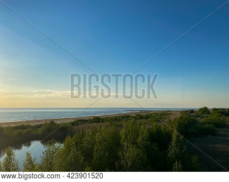 Aerial Shot. Sea Shore With Green Bushes In The Summer Evening With A Sunset Sky.