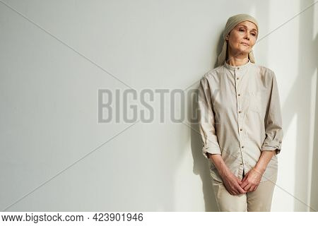 Minimal Portrait Of Pensive Mature Woman Wearing Headscarf While Standing By White Wall In Sunlight,
