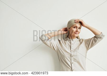 Minimal Waist Up Portrait Of Smiling Mature Woman Wearing Headscarf And Looking At Camera While Stan