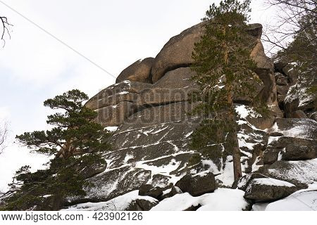 Massive Rock Partially Covered With Snow In The Park.