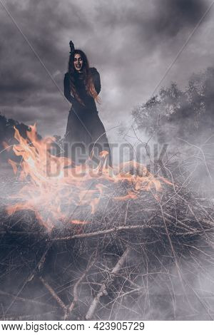 Halloween horror movie. An angry witch tied for incineration. Magic, dark force, spell.