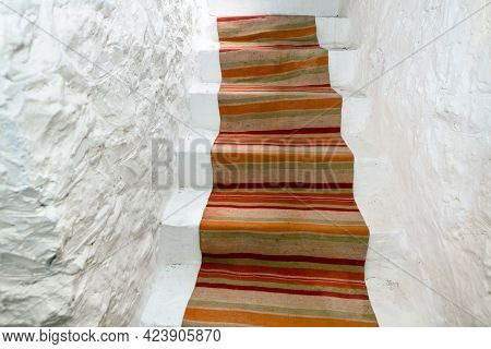 Stairs Covered By Traditional Carpet . White Walls And  Staircase . Entrance To The Wine Cellar