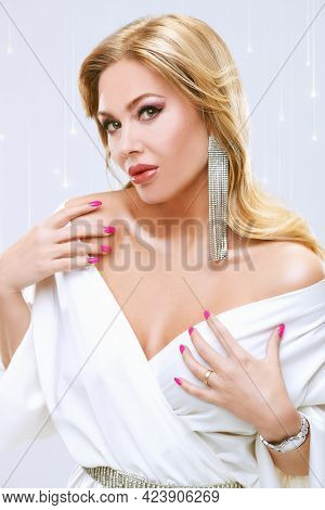 Beauty, fashion. Portrait of a stylish sexy middle aged woman with enlarged full lips and evening makeup posing in precious jewelry. White background with festive lights.