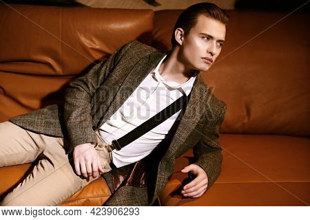 Men's fashion. Well-groomed young man in elegant clothes lies on a leather sofa in a modern luxurious apartment. Business style, businessman.