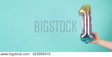Hand Is Holding Balloon Number 1 On Mint Or Tiffany Blue Background.