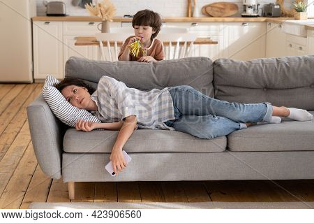 Young Mother Annoyed With Hyperactive Kid. Depressed Woman Mom Or Nanny Lying On Couch Stressed With