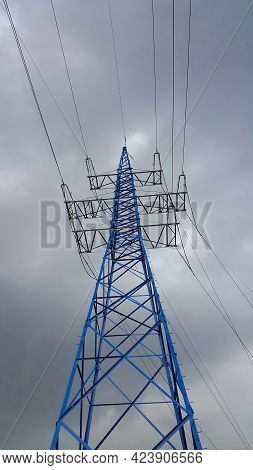 High Voltage Post Or High Voltage Tower Against The Cloudy Sky