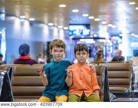 Two Young Brother Boy Dreaming Of Becoming A Pilot. A Child With A Toy Airplane Plays At Airport Wai