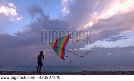 Kid Playing On Beach On Seashore, Child Flying Kite At Sunset On Ocean, Girl On Coastline In Summer