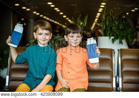 Two Young Kids Sitting On Brown Chairs, Holding Passports And Tickets In Waiting Hall In Airport. Tr