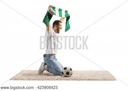 Ecstatic young man with a scarf kneeling and cheering with a scarf and soccer ball isolated on white background
