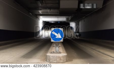 Blue Traffic Sign With Directional Arrow And Two Lanes